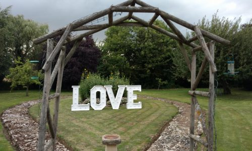 Traditional white LOVE letters under an arch at a garden party
